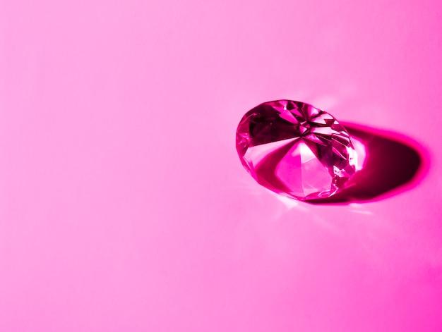 Glänzender kristalldiamant auf rosa hintergrund