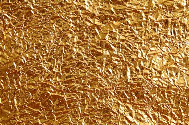 Glänzender metallgelber goldener beschaffenheitshintergrund. metallisches goldmuster