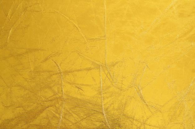 Glänzender metallgelber texturhintergrund. metallisches muster
