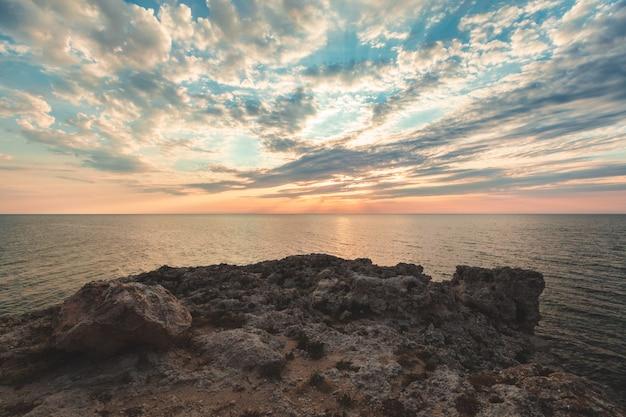 Glänzender urlaubsziel-strandsonnenaufgang und seeklippenhintergrund