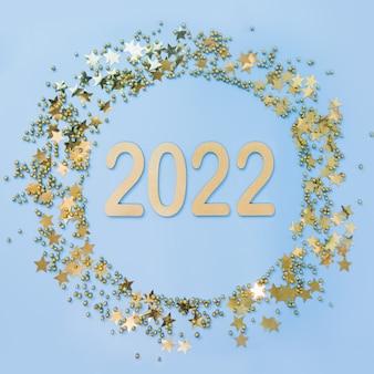 Glänzender weihnachtskranz mit goldenem datum und perlen auf blauem hintergrund mit datum des neuen jahres