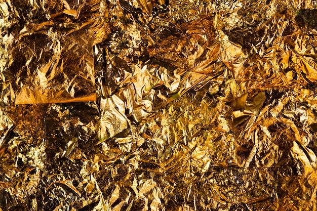 Glänzendes blatt des gelben goldes oder schrotte der goldfolienhintergrundbeschaffenheit