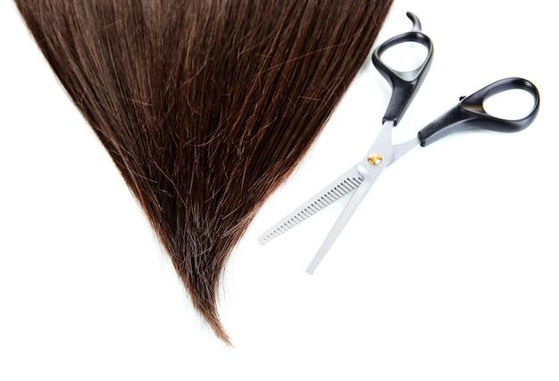 Glänzendes braunes haar mit der schere lokalisiert auf weiß