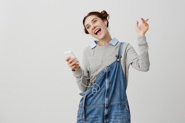 Glänzendes erwachsenes mädchen mit braunen haaren, die wie stern handeln, der neuen entzückenden titel vom smartphone hört. fröhliche frau singt ekstatisch, während sie freizeit verbringt. zeitvertreibskonzept