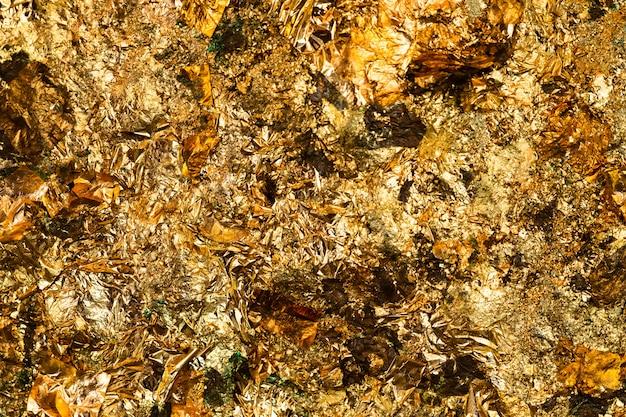 Glänzendes gelbes goldblatt oder schrotte der goldfolienhintergrundbeschaffenheit