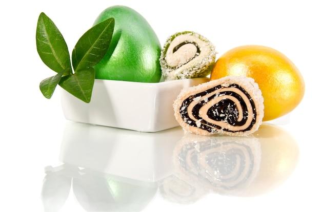 Glänzendes gelbes und grünes osterei auf weiß
