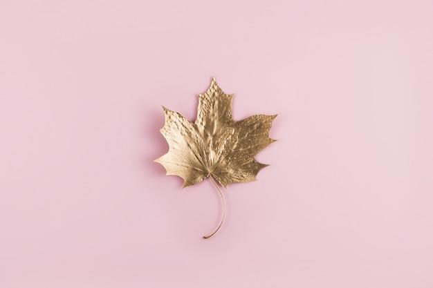Glänzendes goldenes marpleblatt auf rosa draufsicht