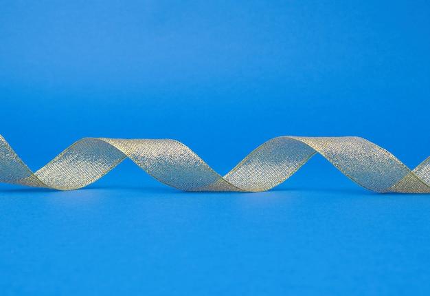 Glänzendes goldenes satinband auf blau