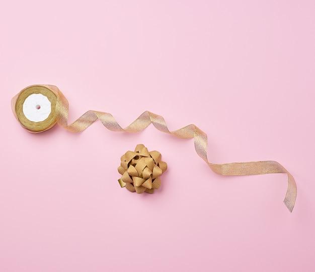 Glänzendes goldenes satinband und bogen auf einer rosa oberfläche
