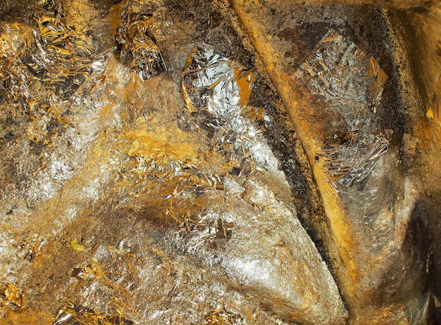 Glänzendes goldfolienpapier auf dem felsenwand-beschaffenheitshintergrund (gold, beschaffenheit, golden)