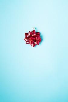 Glänzendes jubiläumsgeschenk und geschenk, das seidiges verzierungskonzept verziert. roter glatter polierter glänzender bogen auf blauem hintergrundausschnittpfadausschnitt