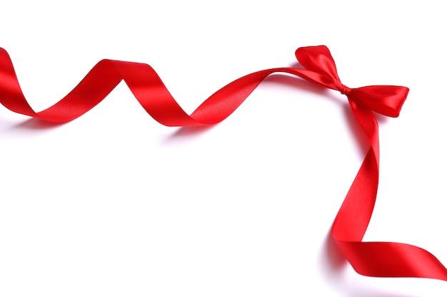 Glänzendes rotes satinband und schleife isoliert auf weiß