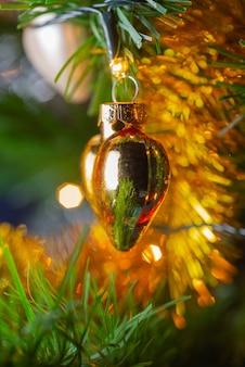 Glänzendes weihnachtsspielzeug in form eines herzens, das an einem weihnachtsbaum hängt.. Premium Fotos