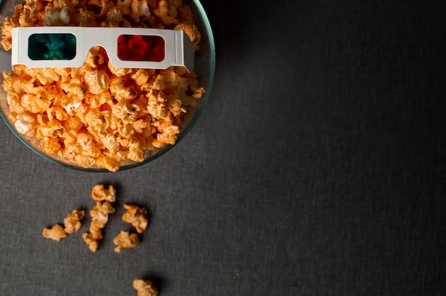 Gläser 3d und popcorn, die auf einem dunklen bett stehen