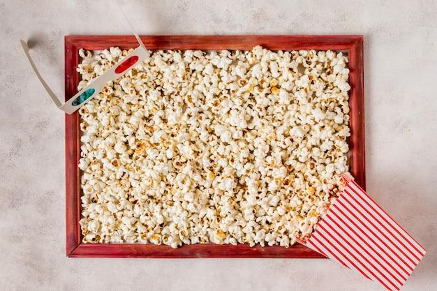 Gläser 3d und popcorn wurden im holzrahmen auf konkretem hintergrund verschüttet
