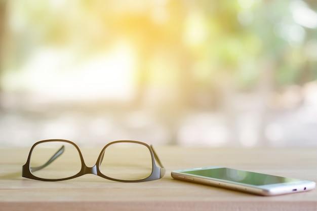 Gläser am telefon liegen auf dem tisch.