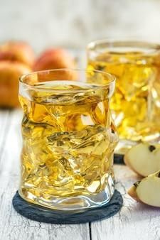 Gläser apfelsaft mit eis und frischem rotem apfel auf einem holztisch an einem sommertag.