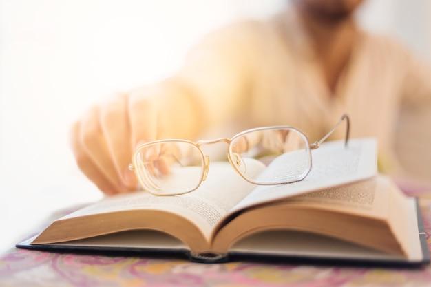 Gläser auf buch mit unscharfem mann im hintergrund