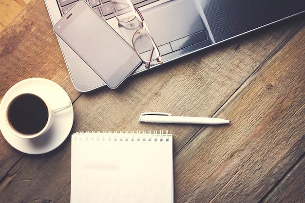 Gläser auf computer, tasse kaffee und papier auf holztisch