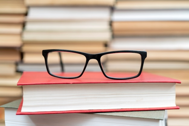Gläser auf dem hintergrund der bücher. symbol für wissen, wissenschaft, studium, weisheit.
