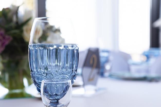 Gläser auf der hochzeitstafel auf einem hellen hintergrund, nahaufnahme