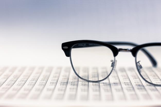 Gläser auf selektivem fokus der finanzberichte an den gläsern analyse der börse.