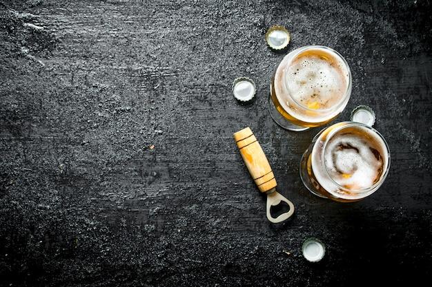 Gläser bier und opener. auf schwarzer rustikaler oberfläche
