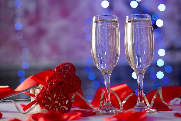 Gläser champagner, herzen und eine geschenkbox zum valentinstag im februar