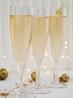Gläser champagner mit goldenen kugeln und lichtern