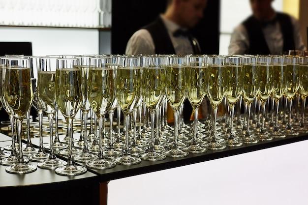 Gläser champagner stehen auf dem tisch. im hintergrund sind zwei kellner