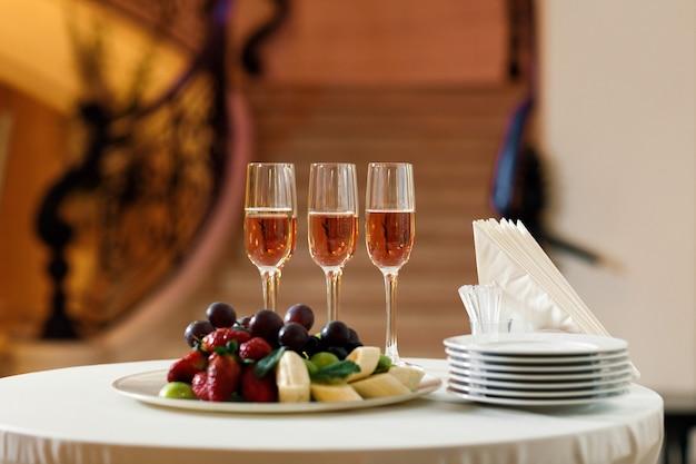 Gläser champagner und ein obstteller auf dem tisch im restaurant. buffettisch