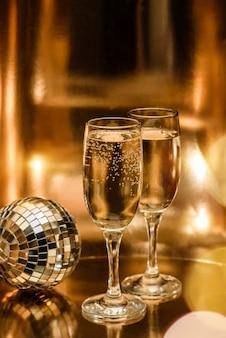 Gläser champagner und eine discokugel auf einer glänzend goldenen oberfläche