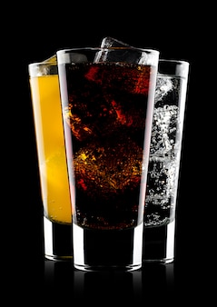 Gläser cola und orangensoda trinken und limonade mineralwasser auf schwarzem hintergrund mit eiswürfeln