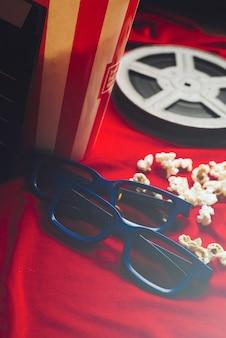 Gläser der nahaufnahme 3d nahe popcorn und spule