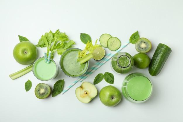 Gläser des grünen smoothie und der bestandteile auf weißem hintergrund, draufsicht