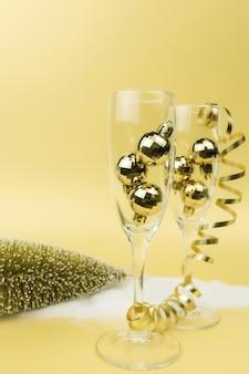 Gläser für sekt, christbaumkugeln, band, goldgrund. foto in hoher qualität