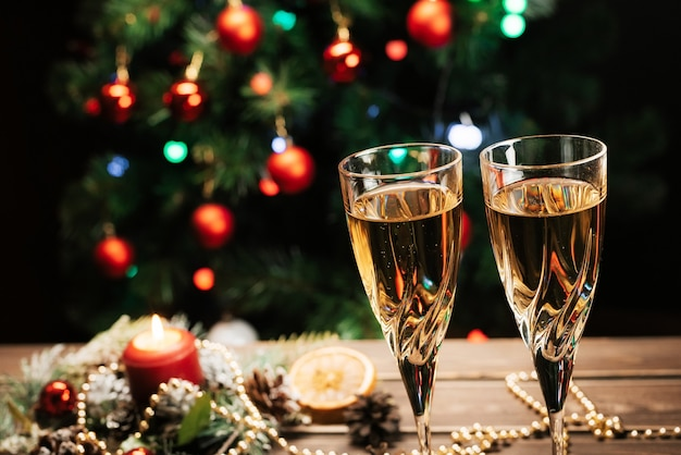 Gläser funkelnder champagner auf dem hintergrund eines geschmückten weihnachtsbaums. neujahrsstimmung