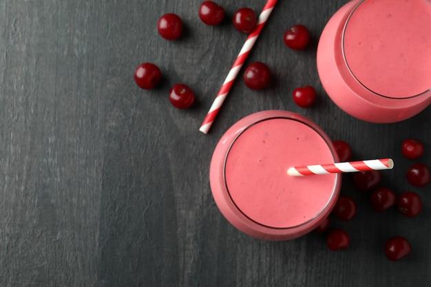Gläser kirsch-smoothie und zutaten auf dunklem holztisch