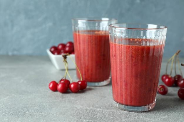 Gläser kirsch-smoothie und zutaten auf grauem strukturiertem tisch