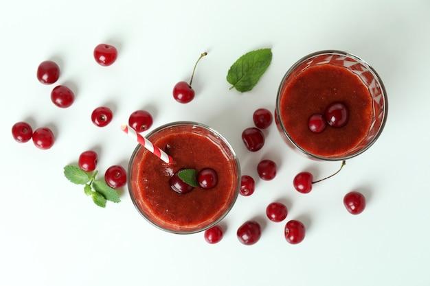 Gläser kirsch-smoothie und zutaten auf weißem hintergrund