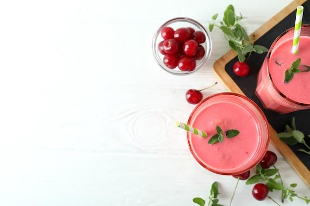 Gläser kirsch-smoothie und zutaten auf weißem holztisch