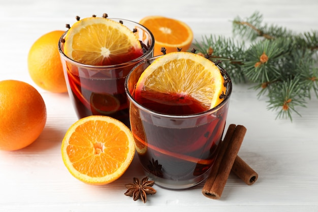 Gläser leckeren glühweins mit orange auf weißem holztisch, nahaufnahme