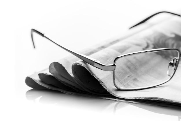 Gläser liegen auf dem stapel zeitungen