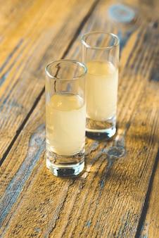 Gläser limoncello auf einem holztisch