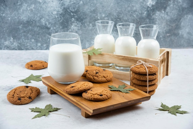 Gläser milch mit schokoladenkeksen und blättern.