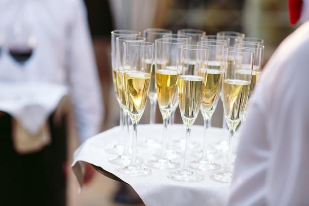 Gläser mit champagner auf einem tablett. die gäste treffen.
