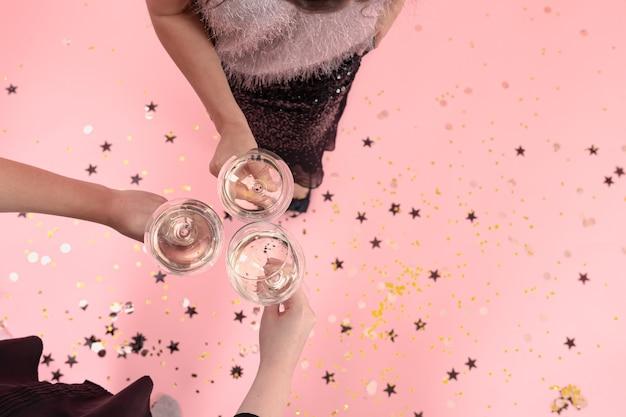 Gläser mit champagner in den händen von mädchen auf einer party auf rosafarbenem hintergrund, kopierraum.