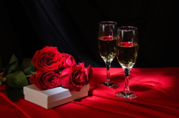 Gläser mit champagner, roten rosen und einem geschenk auf einer roten tischdecke.
