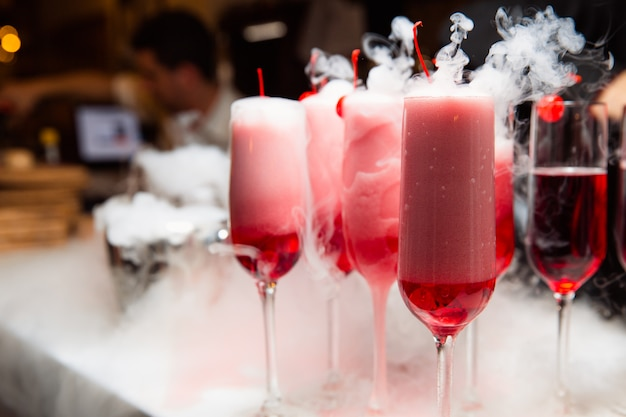 Gläser mit einem roten getränk stehen an der bar. rauch kommt aus dem glas. das glas ist mit kirschen dekoriert.