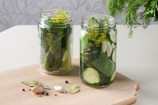 Gläser mit eingelegten gurken mit knoblauch, meerrettich und pfeffer